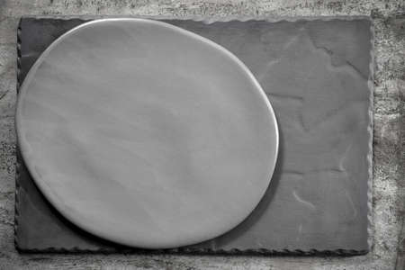 Rustic oval gray plate over slate.  Top view. Stockfoto