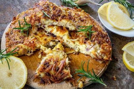 Potato, garlic and rosemary frittata, sliced, with lemon.