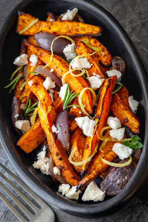 Sweet potato fries with feta cheese and red onion.  In rustic oval black dish.