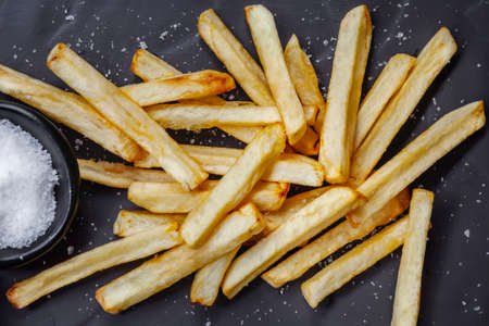 French fries with sea salt, top view, on slate background.