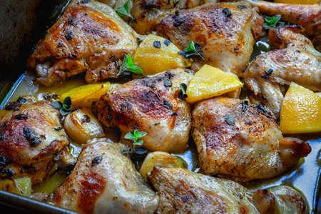 Chicken traybake with lemon, in oven baking dish.