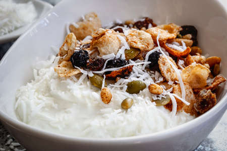 Granola with yogurt and shredded coconut in white bowl, side view.  Healthy breakfast food.