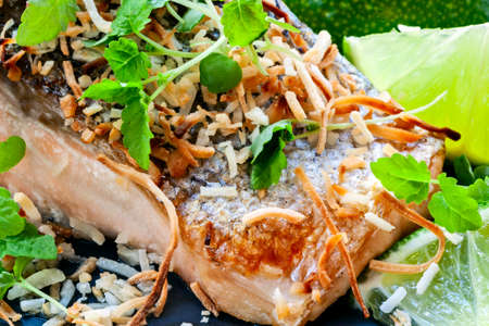 Grilled salmon with toasted coconut, lime, and micro herbs.