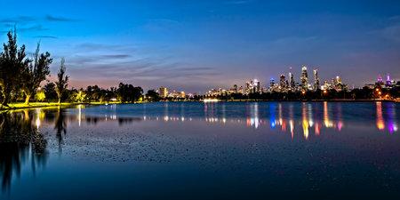 Panoramic skyline of Melbourne, Australia, at night.  Viewed over Albert Park Lake.