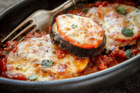 Baked eggplant or aubergine, with tomato and mozzarella, in black dish over slate.