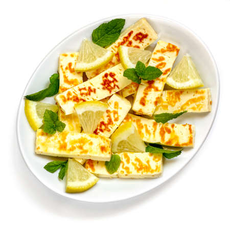 Grilled halloumi cheese on white plate with lemon and mint.  Top view, isolated on white.