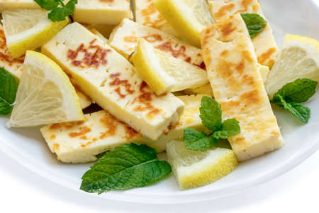 Grilled halloumi cheese with lemon and mint on white plate.  Side view, closeup. Stockfoto