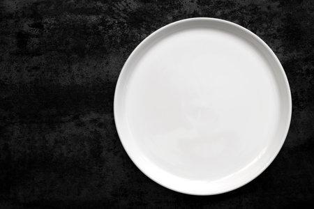 Empty white plate over black slate. Stockfoto