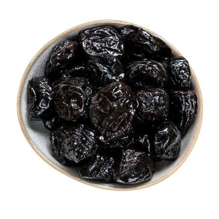 Prunes isolated on white, small bowl, top view.