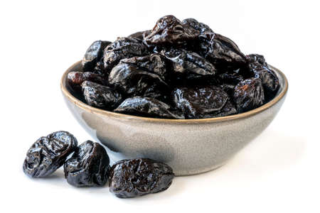 Bowl of fresh juicy pitted prunes over white background.