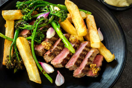 Grilled porterhouse steak with fat french fries, broccolini, shallots and wholegrain mustard.  Top view. Stockfoto