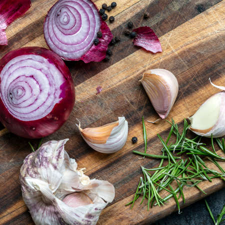 Food preparation.  Garlic, red onions, peppercorns and rosemary on chopping board.  Top view.