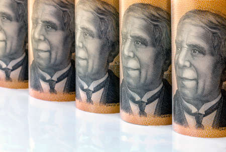 Australian money background.  Rolled fifty dollar notes with focus on faces.