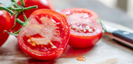 Cut truss tomatoes on chopping board, with knife.  Closeup food background.
