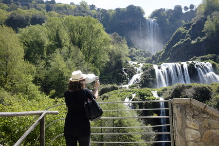 The girl admires Marmore waterfalls with binoculars