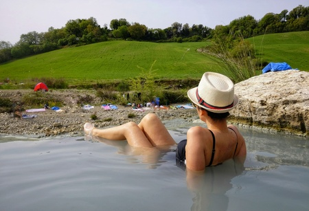 woman enjoys the free spas of Saturnia