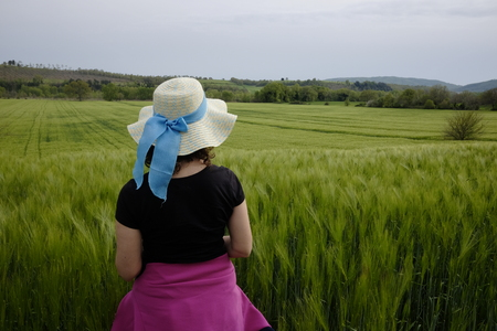 woman admires green wheat field