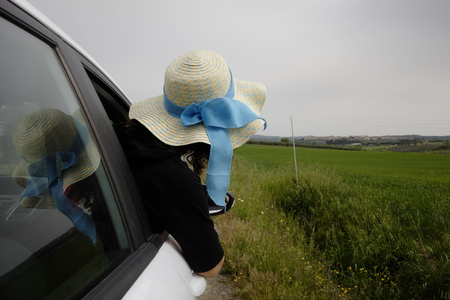 woman with hat looks out of the car window Banco de Imagens