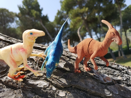 dinosaur toys on tree trunk