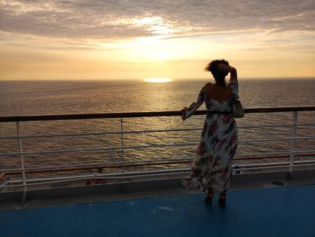 beautiful woman admires sunset from cruise ship