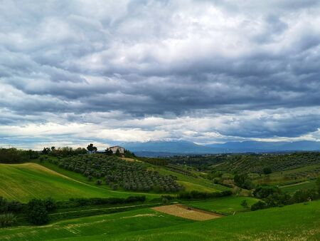 green countryside in spring with threatening clouds