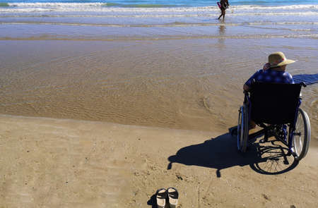 woman in wheelchair by the sea