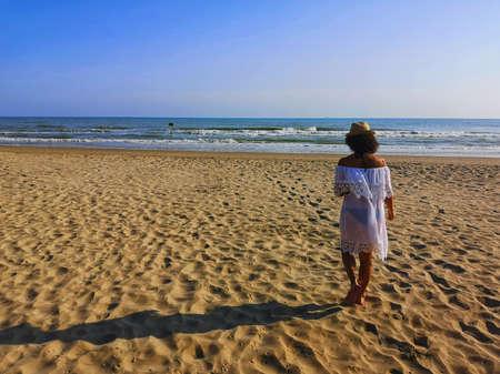 beautiful girl walks on the sand of the sea Foto de archivo