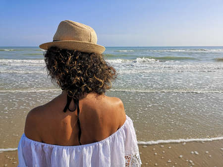 girl from behind with hat looks at the sea