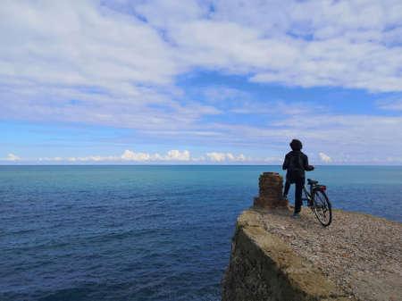 girl on bike on the coast of trabocchi Foto de archivo