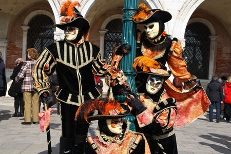 VENICE, ITALY - MARCH 4: Unidentified masked persons pose in front of Palazzo Ducale during the Venice Carnival on March 4, 2011 in Venice, Italy. The carnival is from February 26 - March 8, 2011.