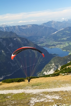 Paragliding above mountain lake Hallstattersee in Alps