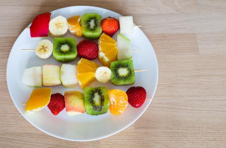 brochetas de frutas: fruit skewers on the plate of the concept of healthy eating Foto de archivo