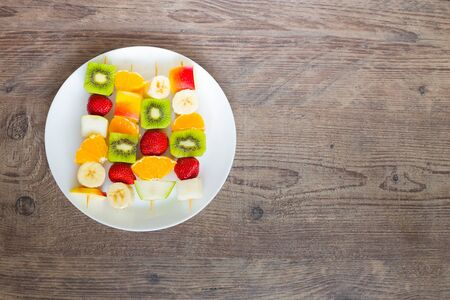brochetas de frutas: plate of fruit skewers with of a place for inscription