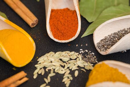 Various spices and herbs on the dark table