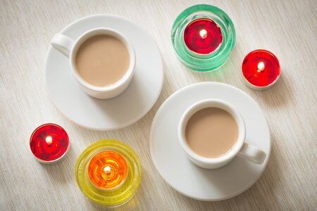 Homemade cup of coffee surrounded by candles Stock Photo