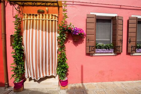 Small, cozy courtyard with colorful cottage   Burano, Venice The small yard with bright walls of houses