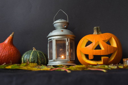 Halloween pumpkins among candles, autumn leaves and moody old lamp