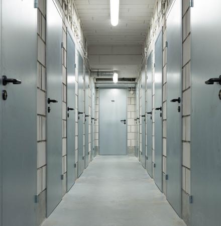 a long corridor in the basement with metal doors