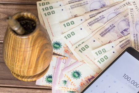 Argentinian money  peso with bombilla and mobile phone with a calculator Stock Photo