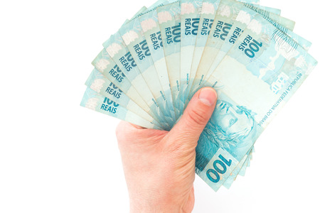 Dinero brasileño, reales, denominaciones altas en la palma de su