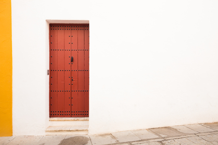 a white-yellow wall with a brown door in the Mediterranean style