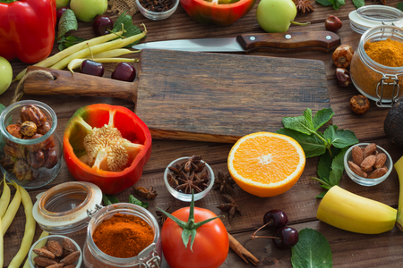 Healthy food, clean food selection:  fruits, vegetables, seeds, spices on brown boards with free space in the middle Archivio Fotografico