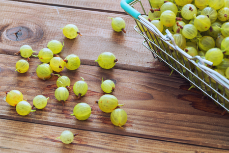 gooseberries in a shopping basket on a wooden table Archivio Fotografico
