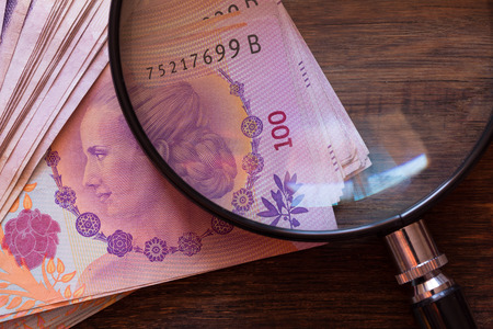 Argentine money, pesos on the table with a magnifying glass Reklamní fotografie