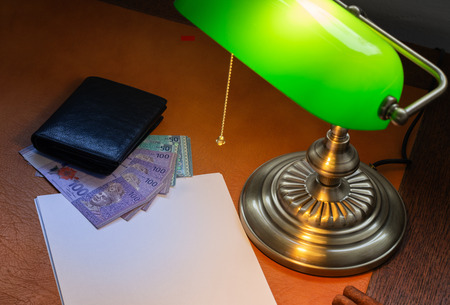Malaysian money, Ringgit, on a stylish desk lit with a banking lamp