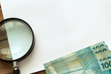 Brazilian money one hundred rais with a magnifying glass and a writing card, a photo from above Foto de archivo