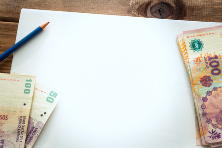 Argentine money, pesos on the table with a white blank card and a pencil Stock Photo - 119512788