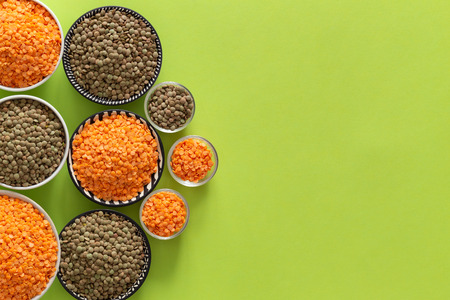Various types of lentils on a green background with space for text Stock Photo