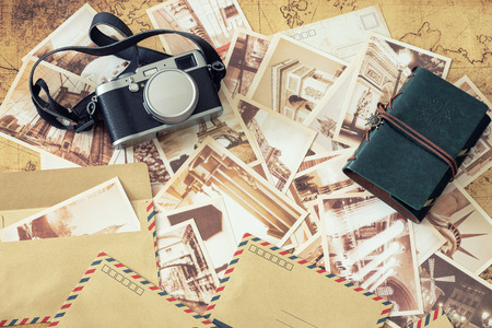 Old postcards with a map, photo camera and travel notebook