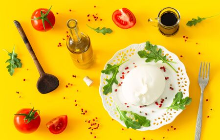 Burrata, Italian cheese with tomatoes, spices, argugula and olive oil and balsamic vinegar / yellow background